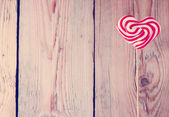 Heart shaped lollipop for Valentine's Day with wooden background — Stock Photo