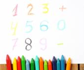 Crayons lying on a paper with painted digit, number, sign — Stock Photo