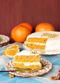 Carrot cake on a wooden table with oranges — Stock Photo
