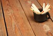 Pencils in a mug on a wooden table — Stock Photo