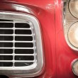 Постер, плакат: Close Up of Grille and Headlights of Red Vehicle