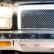 Постер, плакат: Detail of Illuminated Headlight and Grille of Car