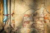 Cracked house wall with hanging metal drainpipe. — Stock Photo