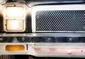 Detail of Illuminated Headlight and Grille of Car — Stock Photo