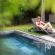 Woman relaxing on chaise longue near pool. — Stock Photo #57770533