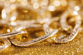 Close up of golden chainlet. gold luxury jewelery. luxe glitter background — Stock Photo