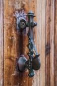 Old iron knoker on an old metal door — Stock Photo