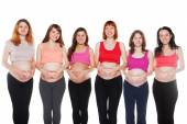 Group of happy pregnant women touching their bellies. Maternity concept. — Stock Photo