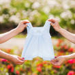 Mothers hands holding a babys clothes. — Stock Photo #65089215