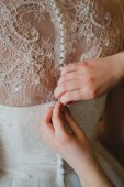 Bridesmaid's hands buttoning wedding dress — Stock Photo