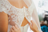Bridesmaid is helping the bride to dress — Stock Photo