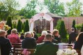 Beautiful wedding ceremony on sunny day. Guests are waiting for groom and bride. — Stock Photo