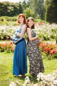 Two beautiful happy pregnant women friends. outdoor. against the background of flowers — Stock Photo