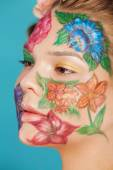 Close up portrait of woman model with hand drawing flowers on her face — 图库照片
