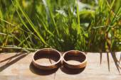 Golden wedding rings laying on wooden table — Stock Photo
