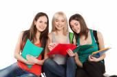 Three students girl with copybooks sitting together on a white background — Stock Photo