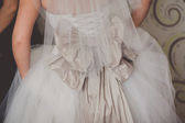 Close up of a wedding dress with large silk bow — Stock Photo