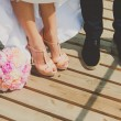 Bride and grooms shoes on the brown wooden floor with bouquet of peonies — Stock Photo #77738600