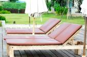Wooden bed arranged beside the pool — Stock Photo