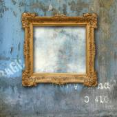 Gold baroque frame on a grunge wall — Stock Photo