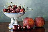 Still life with cherries and peaches — Stock Photo