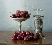 Cherries on a silver plate and an ancient glass — Stock Photo
