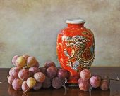 Antique oriental red vase and grapes — Stock Photo