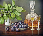 Slivovitz crystal bottle and plums — Stock Photo
