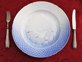 Empty porcelain dish, silverware on damask-cloth — Stock Photo
