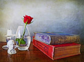 Antiques books, single red rose and other paraphernalia — Stock Photo