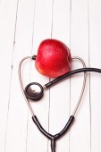 Medical stethoscope and red apple on a white table — Stock Photo