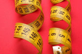 Yellow measuring tape on red background — Stock Photo