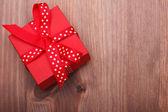 Červená dárková krabička svázané červenou stužku na dřevěný stůl — Stock fotografie