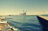 Commerciële dokken bij zonsondergang met een boot en kranen, selectieve aandacht, balchik, Bulgarije — Stockfoto