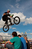 BMX Rider Performs Stunt Over Three Audience Members At Fair — Stock Photo