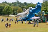 Families Enjoy A Giant Inflatable Shark Slide At Festival Playground — Stock Photo