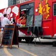 Постер, плакат: Customers Wait In Line To Order Meals From Food Truck