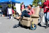 Woman Steers Oddball Furniture Piece On Wheels At Unique Fair — Stock Photo