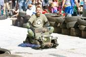 Man Races Miniature Army Jeep At Fair — Stock Photo