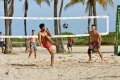 Young Men Kick A Soccer Ball On Beach Volleyball Court — Stockfoto