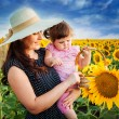 Mother with daughter on the field with sunflowers — Stock Photo #68935223