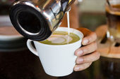 Barista hands pouring milk making hot green tea — Stock Photo