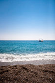Boat on blue sea and rock beach — Stock Photo