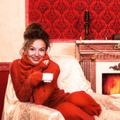 Smiling girl with a cup of coffee in christmas evening in red vi — Stock Photo