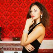 Fashion glamour woman on red vintage wall with a burning candle — Stock Photo