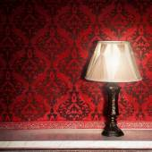Vintage lamp on old fireplace in room with red rocco pattern — Stockfoto