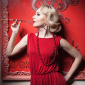 Sensual woman red dress smoking in vintage room — Stock Photo