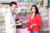 Pharmacist with client inside pharmacy — Stock Photo