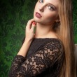 Sexy woman in black dress on green background — Stock Photo #63037061