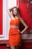 Woman in orange dress on red retro wall — Stockfoto